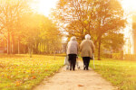 Two elderly women walking in the park.