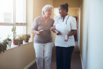 Elderly woman and her nurse walking together in a nursing home.